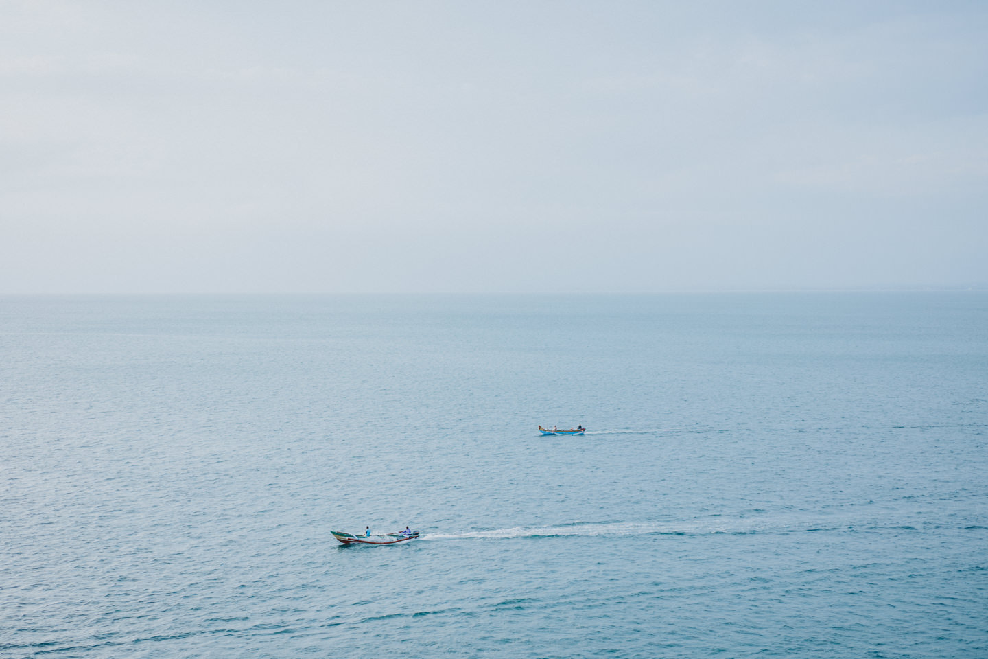 Two boat are passing by on the ocean far