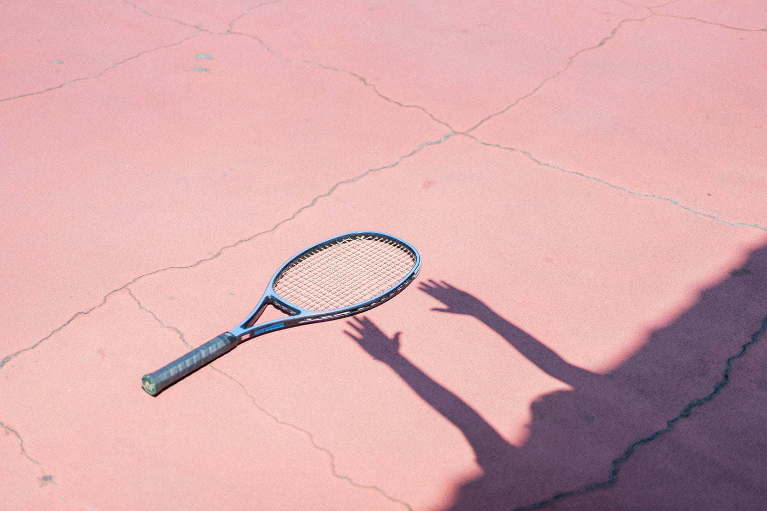 Shadow of hands reaching the tennis racket