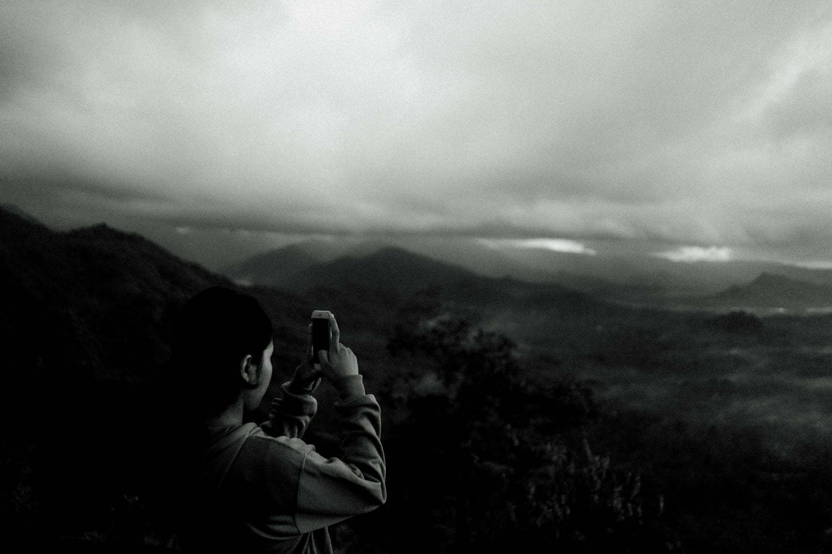 A girl shooting the morning landscape using her phone.