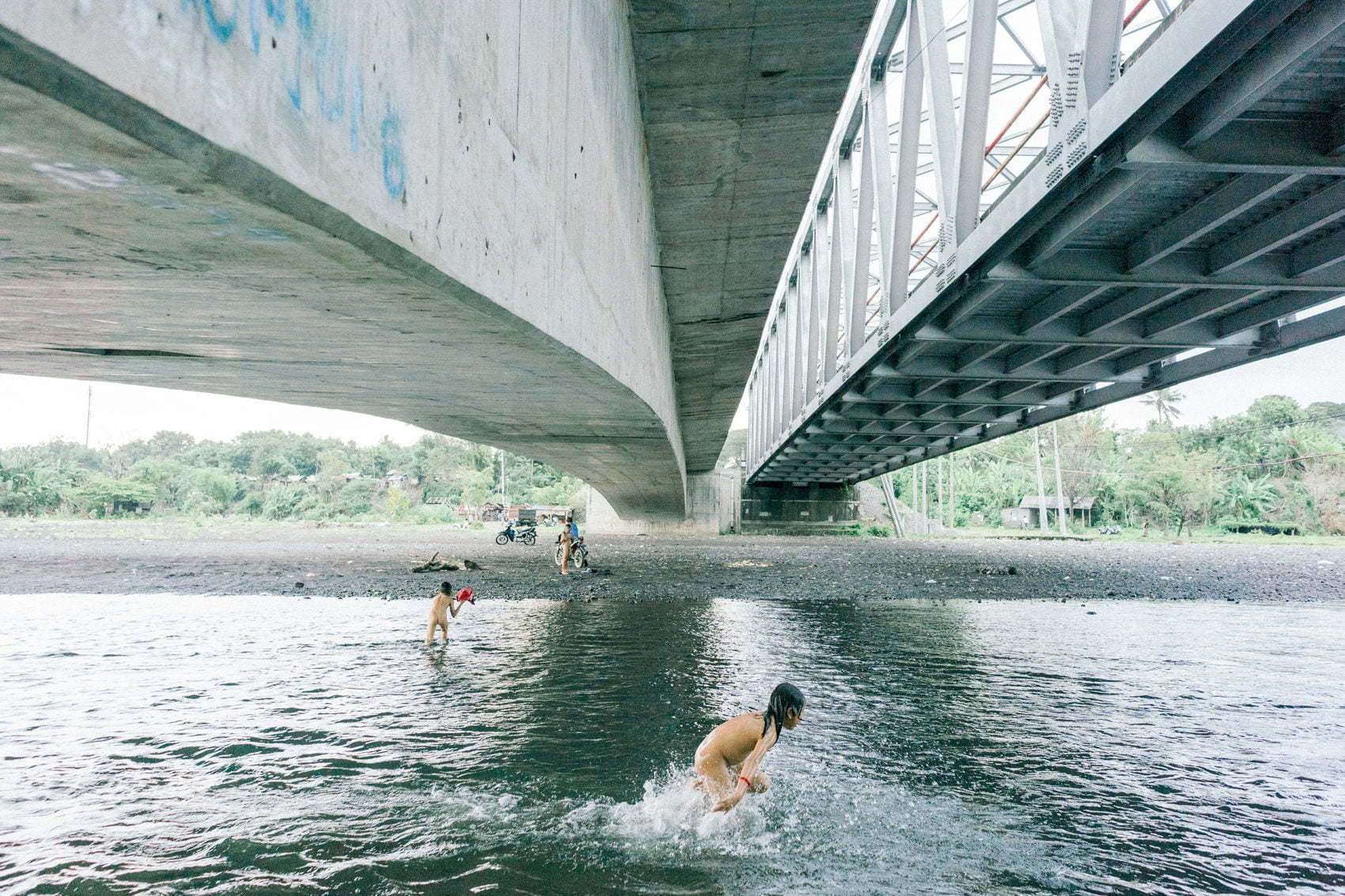 Children take a bath in the river under the bridge