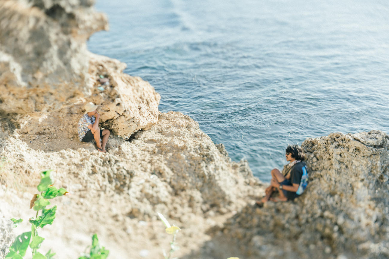 Two people waiting the sunset in the cliff side