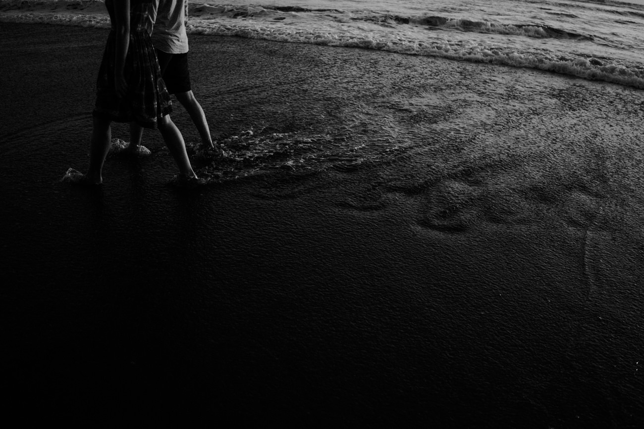The couple walk in the shore line with the wave